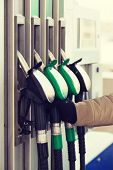 Постер, плакат: vehicle and fuel concept close up of male hand holding fuel pump at fuel station