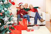 Senior couple and grandson celebrating christmas at home with gifts