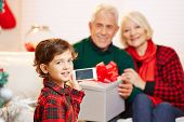 Child taking smartphone picture of grandparents at christmas