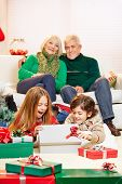 Two surprised children opening gifts at christmas with grandparents