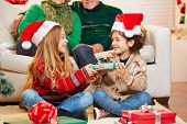 Siblings giving gifts to each other at christmas at their grandparents