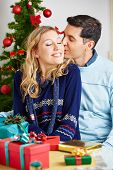 Man kissing smiling woman while she wraps christmas gifts