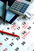 A checkbook, bills, a calculator and a calendar