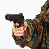 Hand in camouflage uniform with army handgun on white background