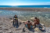 Three unidentified boys cleaning freshly caught fish on Playa Sana Rafael in Dominican Republic