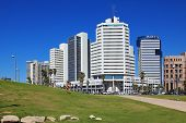 TEL AVIV, ISRAEL - MAY 2, 2014: Modern magnificent hotels skyscrapers and green lawns. The picturesque Tel Aviv promenade in sunny spring day