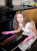 Annoyed Woman Cleaning The Oven