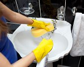 stock photo of cleaning service  - Young woman cleaning a bathroom - JPG