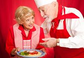Senior woman gets a lesson in cooking from an Italian chef.