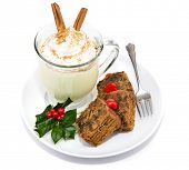 Plate of Christmas fruitcake and delicious frothy eggnog isolated on white.