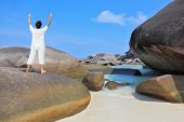 Thailand. Gorgeous beach on the Similan Islands. Middle-aged woman dressed in white doing yoga.  Pose