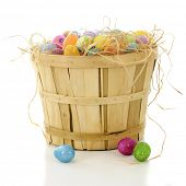 A bushel basket filled with straw and colorful Easter eggs.  On a white background.