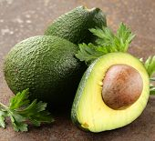 fresh organic ripe avocado with leaves of parsley