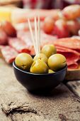 picture of charcuterie  - Charcuterie assortment and olives on wooden background - JPG