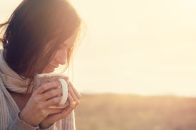 pic of cold drink  - Woman wearing warm knit clothes drinking cup of hot tea or coffee outdoors in sunlight - JPG