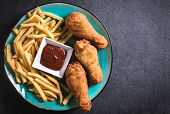 image of fried chicken  - French fries and fried chicken legs on dark background with blank space - JPG