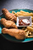 picture of fried chicken  - Fried chicken legs and French fries with bbq sauce in the plateselective focus - JPG