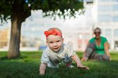 picture of crawl  - Baby crawling on the grass on a background of sitting his mom - JPG