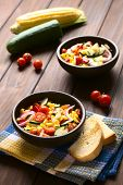 stock photo of sweet-corn  - Bowls of fresh vegetable salad made of sweet corn cherry tomato cucumber red onion red pepper chives with toasted bread on the side photographed on dark wood with natural light  - JPG