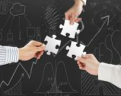 picture of comrades  - Group of business people assembling blank white jigsaw puzzles on business concept doodles background - JPG