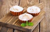 picture of bakeshop  - Homemade Muffins Ready for Breakfast on a board on wooden background - JPG