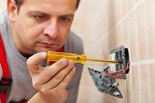 image of electrician  - Electrician checking wall fixture with voltage tester before unmounting it - JPG