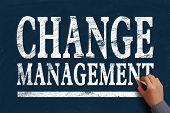 image of change management  - Businessman is writing Change management text on blue chalkboard - JPG