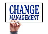 stock photo of change management  - Businessman is writing Change management concept on transparent white board - JPG