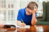 pic of homework  - Portrait of a little kid having problems with his homework and trying to think  - JPG