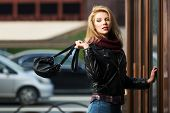 foto of mall  - Young fashion blond woman with handbag at the mall door - JPG