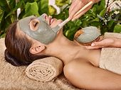 stock photo of facials  - Woman with clay facial mask in beauty spa - JPG