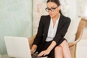 picture of comfort  - Confident young woman in formalwear working on laptop while sitting at the comfortable chair - JPG