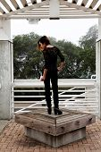 stock photo of black pants  - Skinny Asian American Woman Standing Outdoors Black Pants - JPG