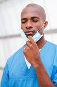 image of african mask  - Portrait of tired young African doctor in blue uniform taking of his surgical mask and keeping eyes closed - JPG