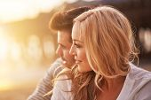 foto of sun flare  - pretty girl cuddling with boyfriend on beach at santa monica with shallow depth of field and bright warm lens flare - JPG