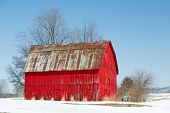 picture of red roof  - A vivid red wooden barn is topped with a rusty metal roof in a snowy landscape under a clear blue sky.