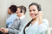 pic of telemarketing  - Portrait of smiling female customer service executive with colleagues in background at office - JPG
