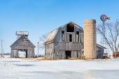 foto of silos  - Old barns with a silo and windmill stand in a snowy Indiana landscape.