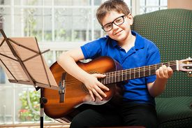 image of tween  - Cute blond tween with glasses playing the guitar at home and smiling - JPG
