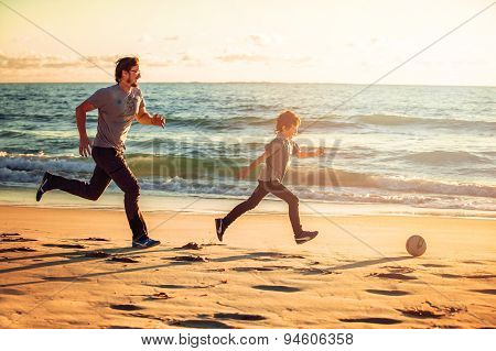 Happy father and child play soccer or football on the shoreline in dusk light