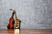 stock photo of saxophones  - Violin and saxophone on gray wall background - JPG