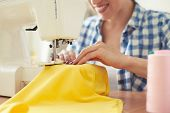 image of sewing  - smiley woman sewing on sewing - JPG
