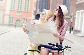 pic of tandem bicycle  - A picture of two girl friends using a map and riding a tandem bicycle in the city - JPG
