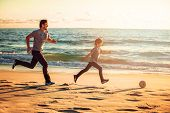 Happy father and son play soccer or football on the beach in sunset light poster