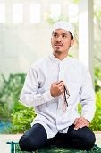stock photo of prayer beads  - Asian Muslim man praying at home sitting on prayer carpet in his house in front of the tropical garden - JPG