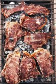 pic of charcoal  - fresh hot bbq grill red beef meat steak ready on grid over charcoal with marks - JPG