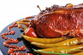 pic of red meat  - roast red beef meat bbq block served on black plate  with green chives and red hot pepper on black plate isolated over white background - JPG