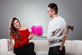image of sneaky  - Sneaky insincere man holding axe giving gift present box to woman - JPG
