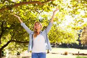 picture of open arms  - happy young woman with arms open under the trees - JPG