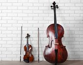 image of cello  - Cello and violin on bricks wall background - JPG